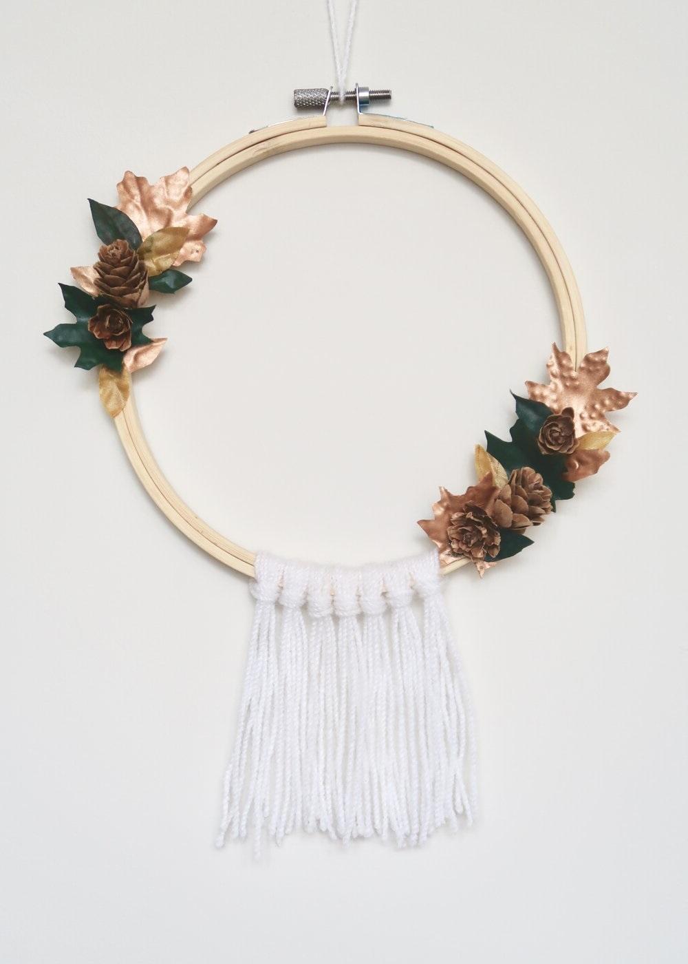 Bricolage d'automne: couronne de pommes de pin et feuilles en papier.